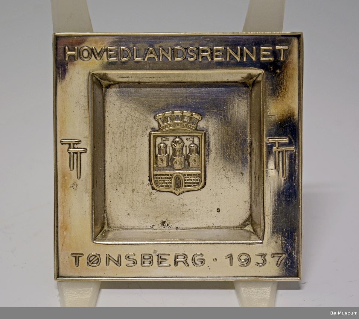 "Liten, firkantet sølvskål med innskrift: ""HOVEDLANDSRENNET - TØNSBERG 1937"" Tønsbergs byvåpen. Uten stempel - ikke sølv."