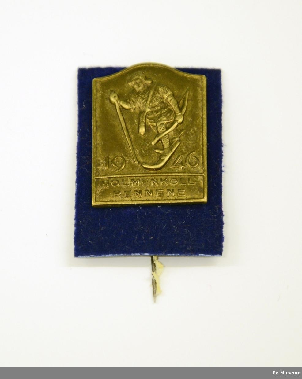 """Pin med innskrift: """"HOLMENKOLLRENNENE 1946"""" og """"birkebeiner"""" Messingplate montert på plate med blå plastplate med """"fløyel"""" (og nål)"""