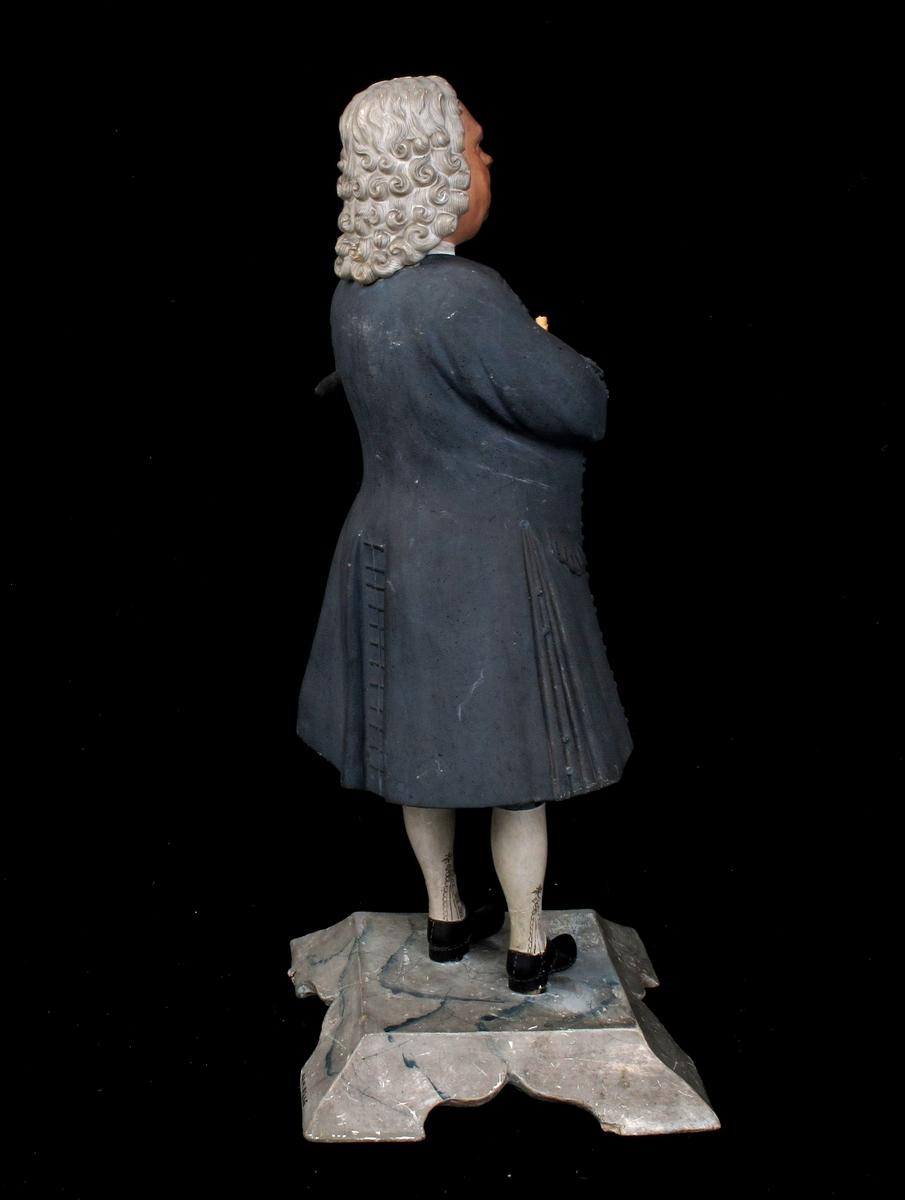 Statuett av stående, eldre mann i helfigur,  frontal med v. ben foran, h. ben med foten ut til siden.  Rødbrun karnasjon, lys gråhvit tettkrøllet parykk med håret  ned til frakkekragen. Hvit skjorte sort tettknappet  vest med øvre del uknappet, v. hånd innenfor vesten  og h. hånd fremstrakt med en papirrull.  Over vesten blågrå åpen frakk med sidelommer,  folder i sidene og en motfold midt bak.  Splitt i ermen til albuen, tresnutet hatt under