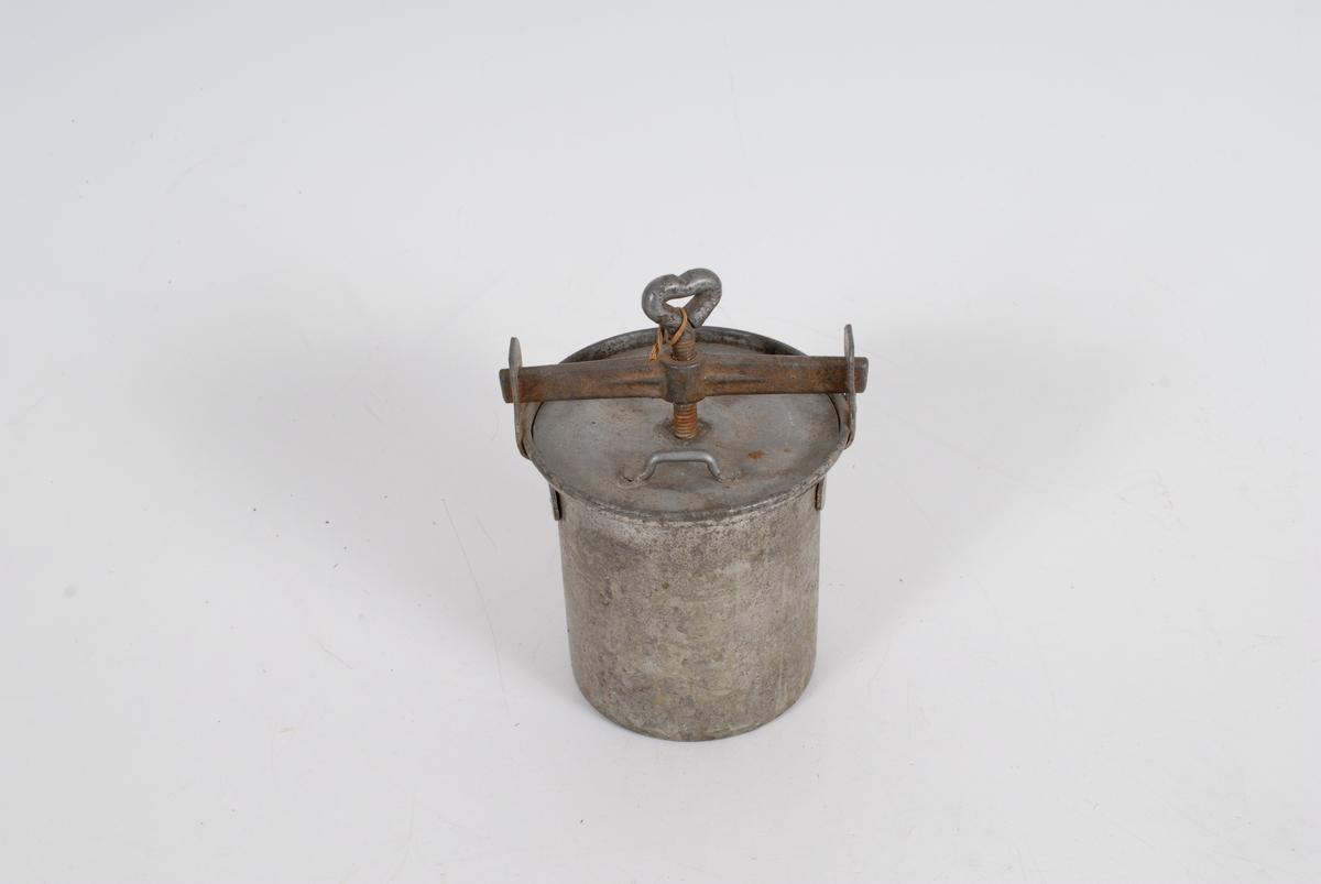 Form: sylinder, med lokk som festes med en skrumekanisme, ekstra lokk inni