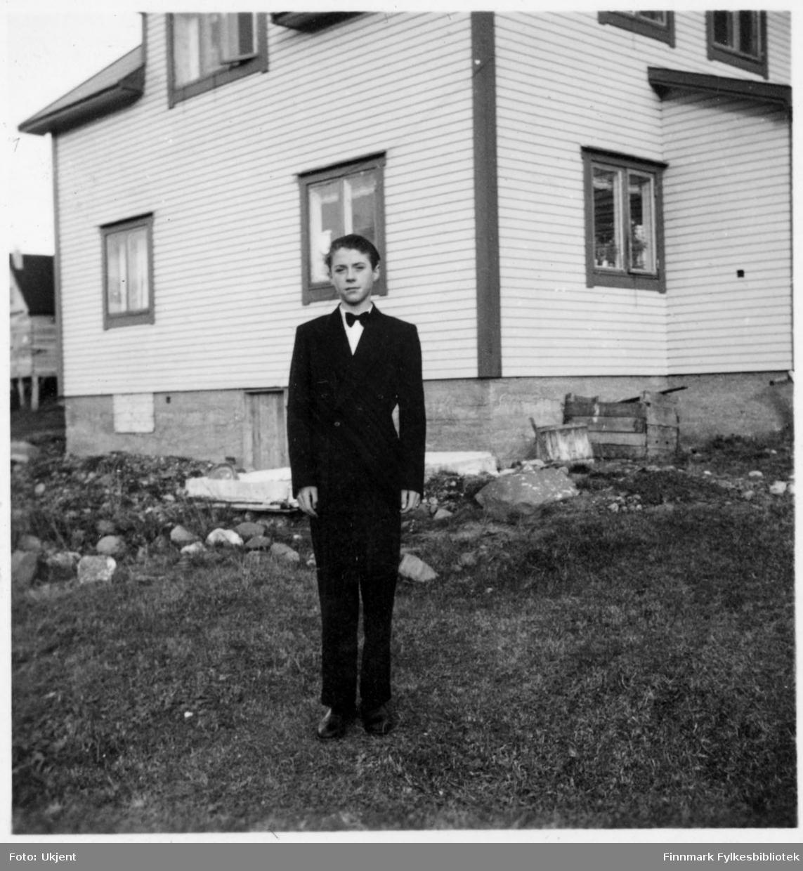 Odd Martinsen som komfirmant.Han er kledd i dress: jakke, bukser og sløyfe rundt halsen. Han står utenfor et hus med vindu. Det står et par trekasser mot grunnmuren.