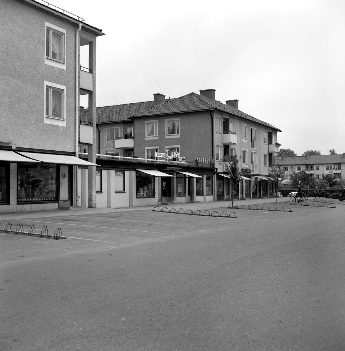 """Någonstans i Värmland - från slutet av 1950-talet. Kommentar från användare: """"Skoghalls centrum. Affärslänga Clevevägen Skoghall""""."""