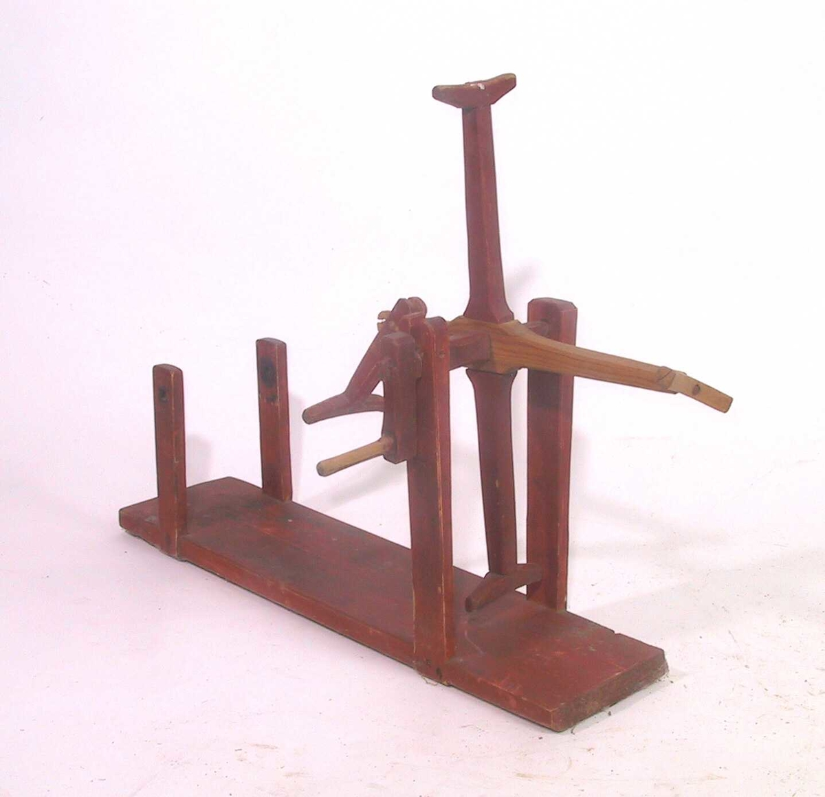 Hespetre, rødmalt. Rektangulært fotbrett med to lave og to høyere vertikale ledd i hjørnene.  I de høye er en aksling med 4 armet  med tverrledd ytterst.