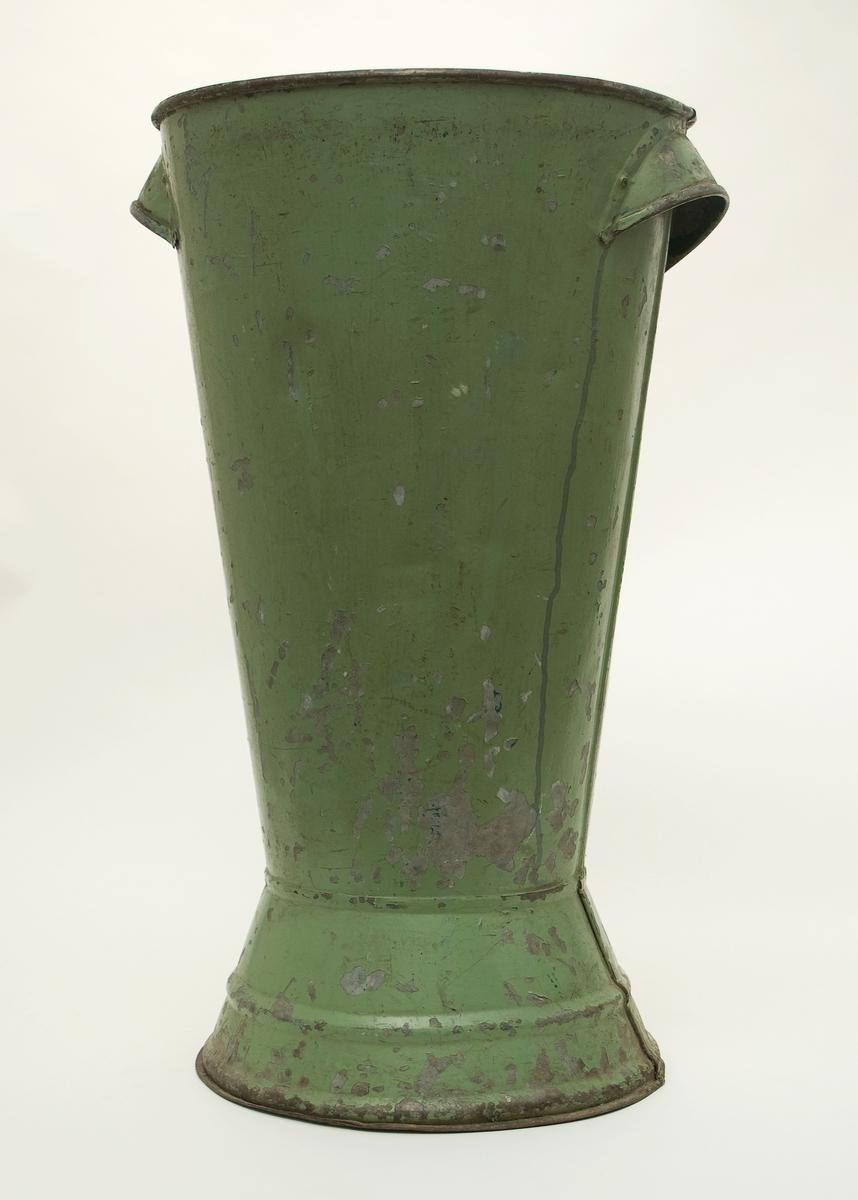 Vas av grönmålad bleckpåt för snittblommor att exponera blommorna i vid försäljning. Färgen delvis bortnött.