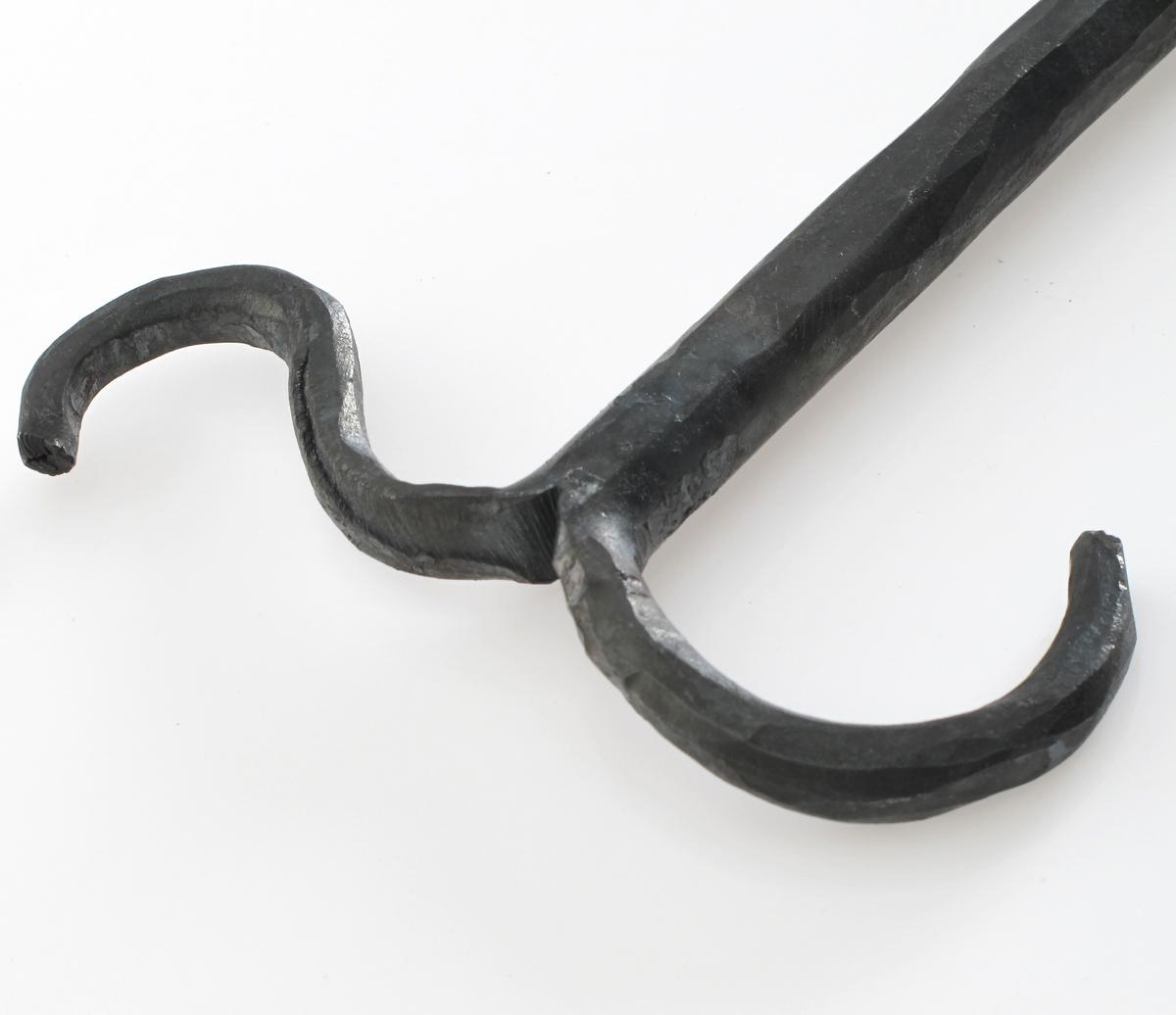 """Rund bøyle som passer rundt en hals, med to lange  """"armer""""  med kroker i enden. Kan låses rundt halsen."""