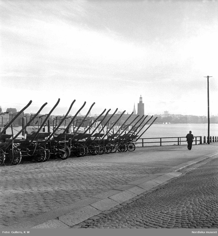 Stockholm, Söder Mälarstrand. Hästkärror uppställda på rad längs kajkanten. Riddarfjärden och Stadshuset i bakgrunden.