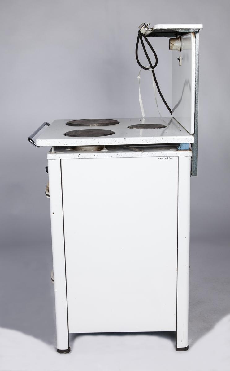 FHM.06488a: Elektrisk komfyr med tre plater, varmeskap og stekeovn. Bakplate med lys. FHM.06488b: Stekeovnsplate 31x40cm. FHM.06488c: Stekeovnsplate 31x40cm.