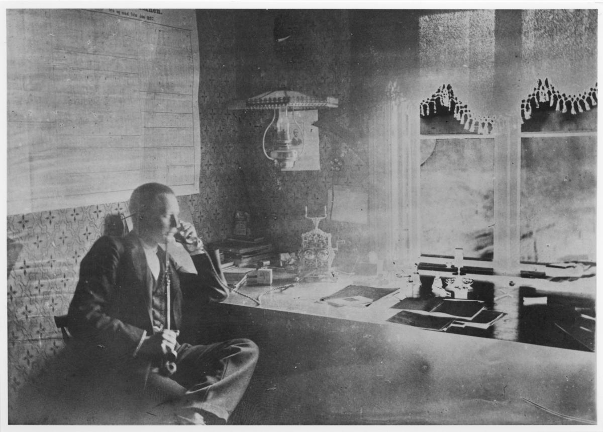 Bildet er mest sannsynlig tatt på Sætra gård, der Urskog-Hølandsbanen skal ha leid kontor. Det er mindre sannsynlig at bildet er tatt på Bingsfos stasjon. Rutetabellen på veggen er datert 1. juni 1897.