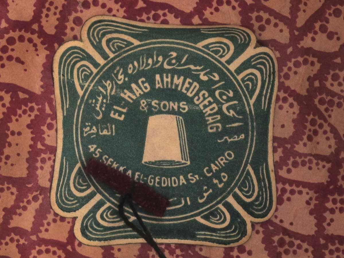 Hodeplagg, nesten sylinderformet. Rødt, filtlignende tøy på yttersiden rundt en kjerne av tynn kartong. På innsiden papir, av tre ulike  kvaliteter. Etikett med arabiske og latinske bokstaver. Dusk av sorte tråder.