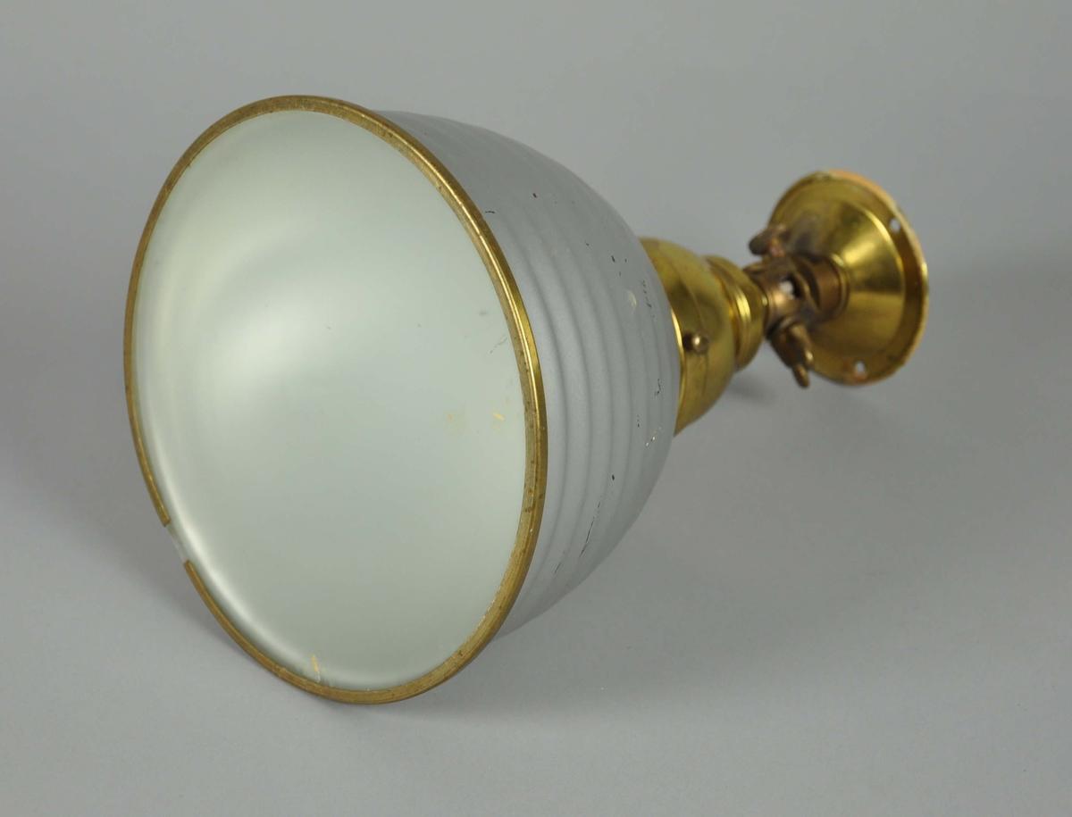 Skjermen er av grått metall, veggfeste og pæreholder av messing. Glasset er av frostet glass.