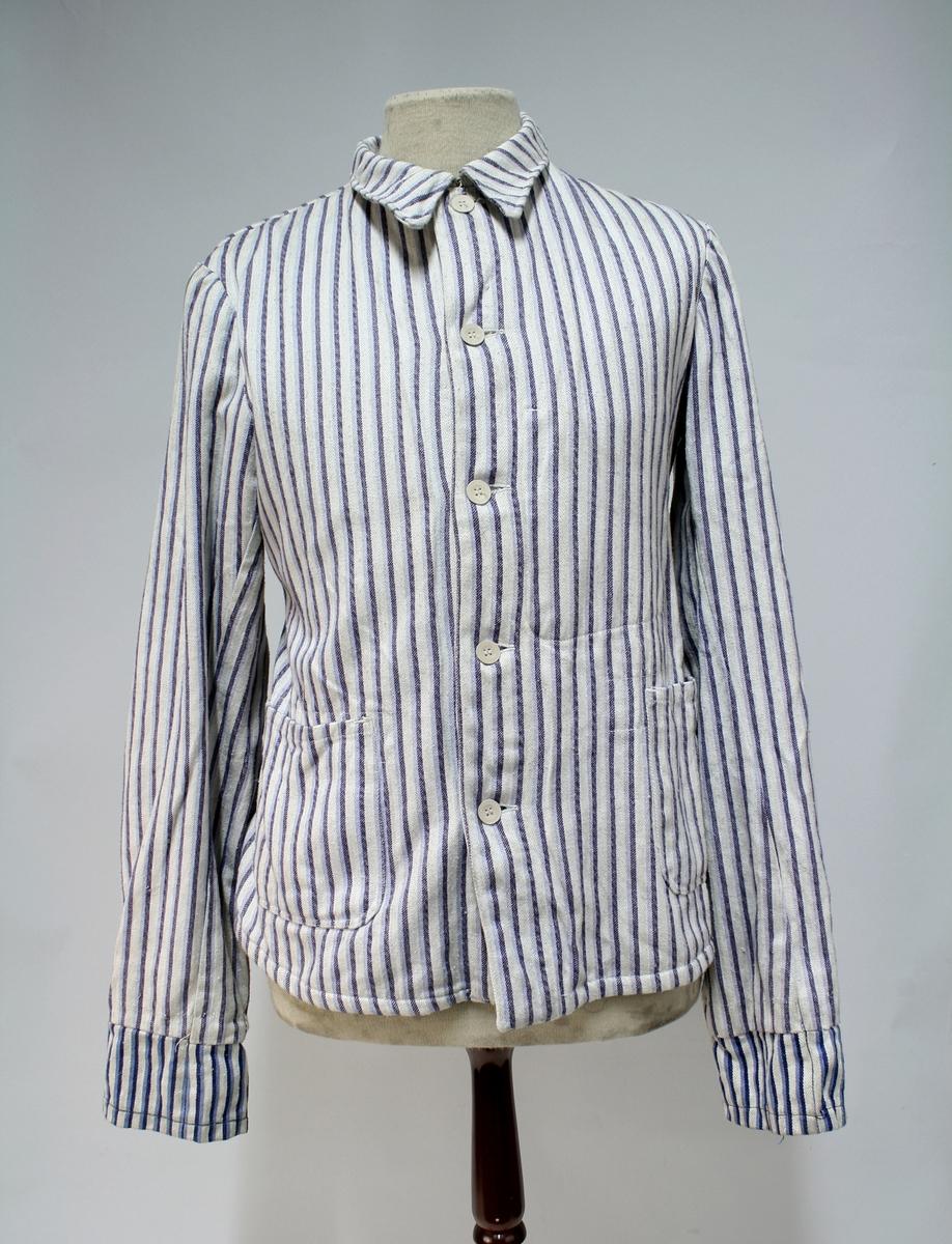Enkel jakke i solid bomullsstoff. To lommer i front og seks knapper. Jakken har påsydd forlengelse av armene og påsydd halvbelte med knapp bak.