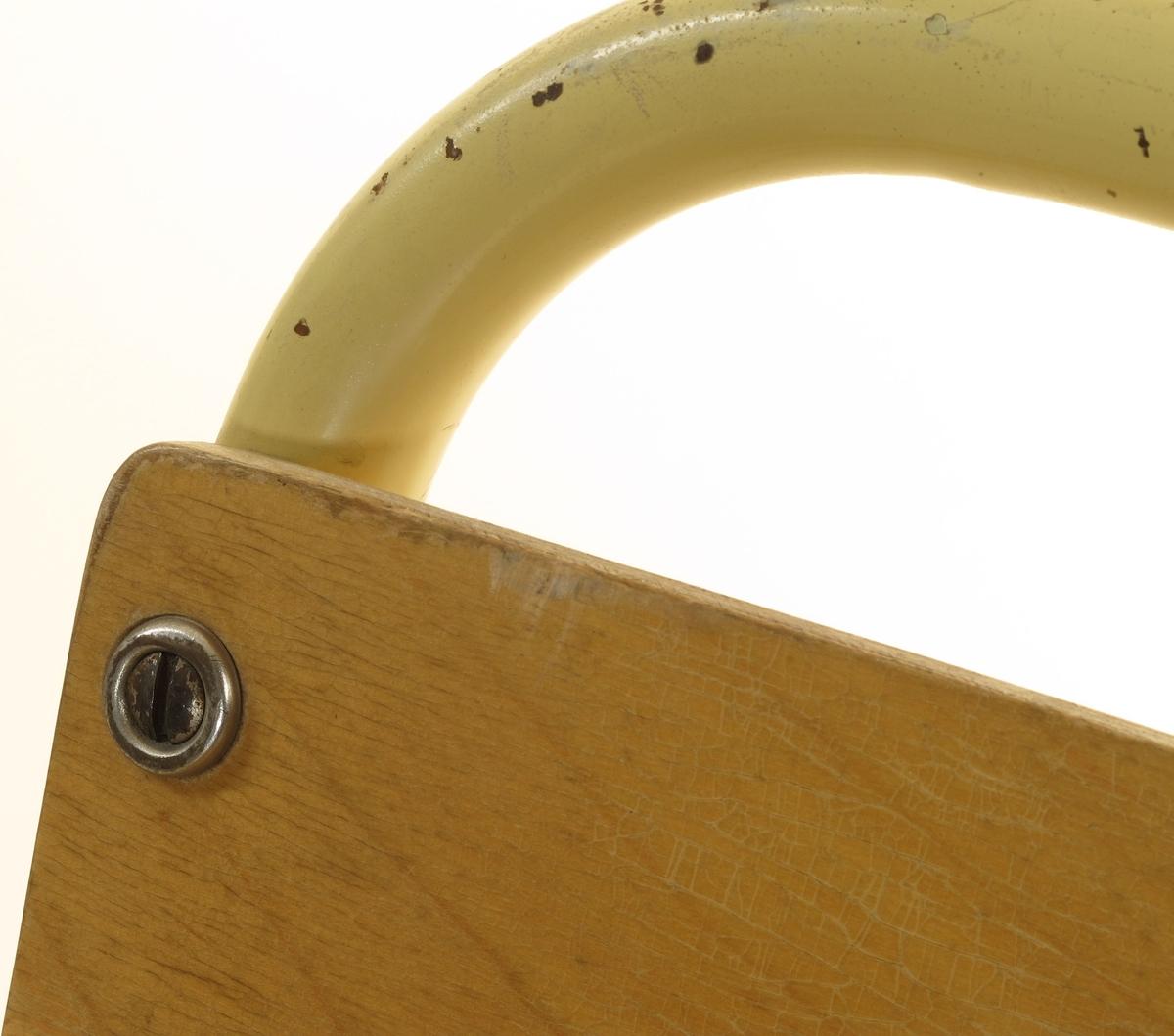 Ramme av stålrør, sveiset sammen. Sete og ryggbrett av knyssfiner. Formet slik at mange stoler av denne type kan stables på hverandre.