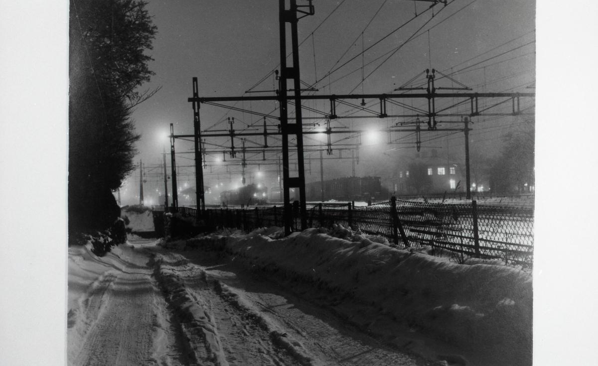 """""""Bangården en vinterkväll"""". Från utställningen """"Falköping i bild"""" 1952."""
