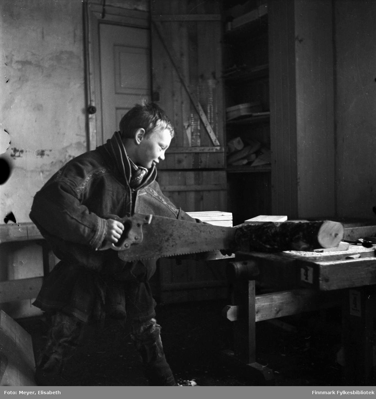 Sløydtime på Kautokeino skoleinternat. Johan Nils Peder Johansen Sara jobber med sag ved høvelbenken.