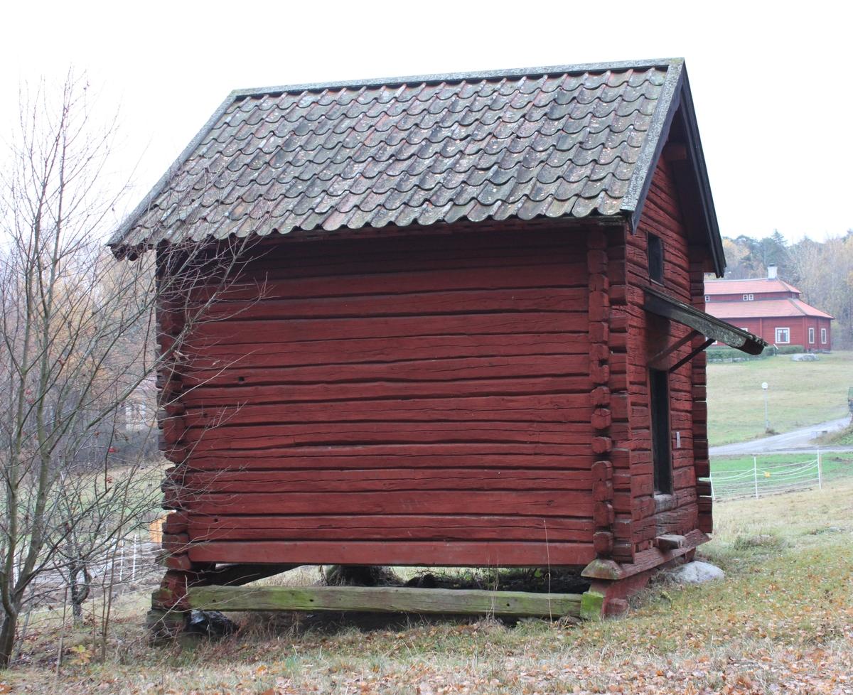 Sädesbod i två våningar och närmast kvadratisk planläggning. Byggnaden vilar på låga stolpar, på fyra grundstenar, i ganska sluttande terräng. Stommen är byggt av fyrkantstimmer med utknutar. Frånsidan mot öster har locklistpanel utom på gavelspetsen samt droppkant av plåt nedtill. Sadeltak klätt med brädtak och enkupigt tegel. Nock- och vattbrädor samt vindskivor av trä. Vindskivorna är dubbla och den nedersta har en profilerad kant. Skärmtak av trä, faltak, över ingången. Låg, svart bräddörr med snedlagd panel. I nedre delen av dörren finns ett runt hål. Ett smitt och vridet handtag samt en nyckelskylt av 1600-talstyp finns på dörren. Denna låses med en ögla och en märla. Två av golvbrädorna skjuter fram och utgör insteg/trappsteg upp till dörren. På övre våningen ovanför dörren finns en trälucka med smidda gångjärn. Interiört består nedervåningen av ett enda stort utrymme. Mot östra fasaden finns ett hålrum med uppgång till övervåningen. Även den består av ett enda stort utrymme, men med avgränsningar, fack, för olika förvaring.