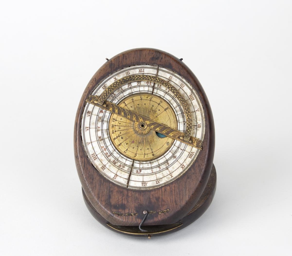 Solur trolig fra 1700-tallet. Instrument for måling av månefaser og solens hellning. Ovalt treobjekt som holdes oppe av en tynn messingpinne, sammelagt ligger to like store ovale treskiver oppå hverandre. På oversiden er det en klokkelignende rund måleskive (astrolabe?) i metall. Treskive to inneholder to kompassliknende skiver som er nedfelt i treverket.