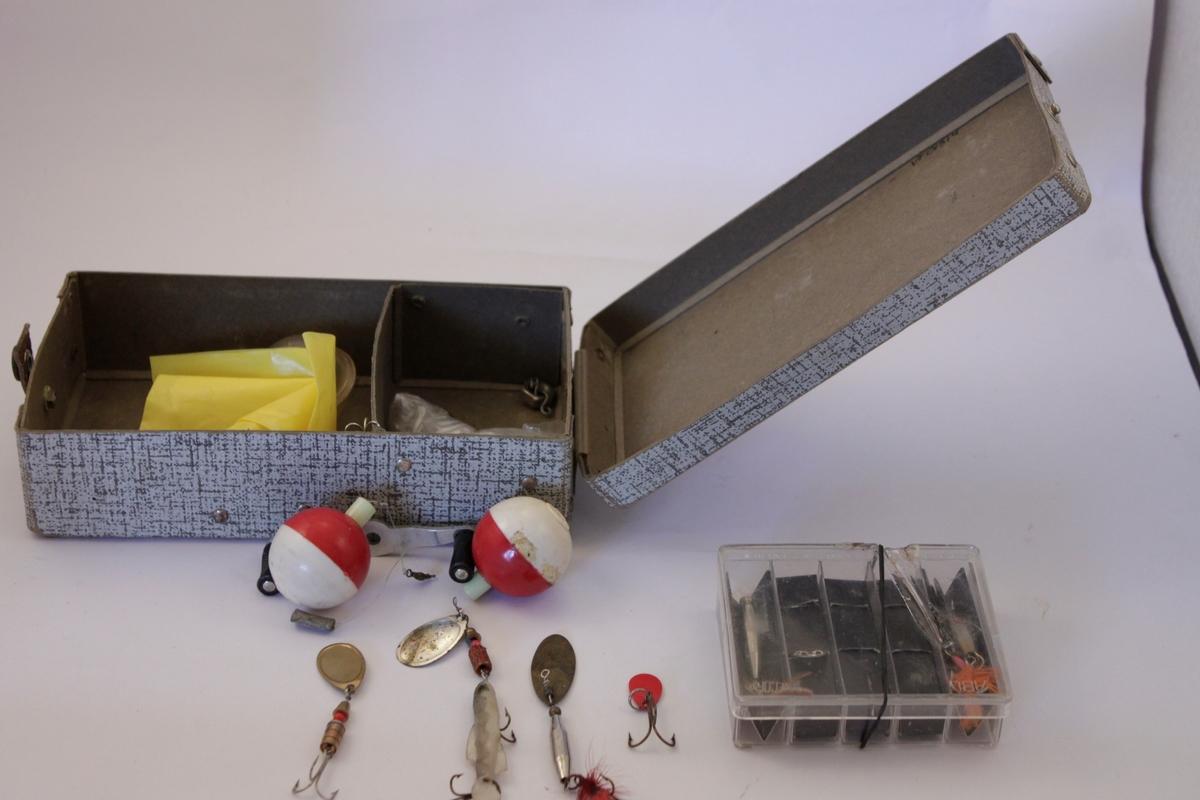 Mönstrad papplåda med lock och röd text FISKEREDSKAP. Locket kan låsas med en läderremsa försedd med tryckknapp. Innehåller flera olika fiskedrag och två flöten.