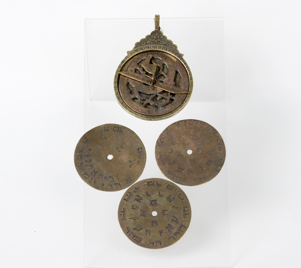 Astrolabium i messing i åtte deler med hebraisk skrifttegn: 5 skiver, 1 viser, 1 stift, 1 pinn m/hestehode. 3 av disse skivene er utstilt sammen med astrolabien.De sirkelformede messingplatene kan skiftes ut og dreies rundt.