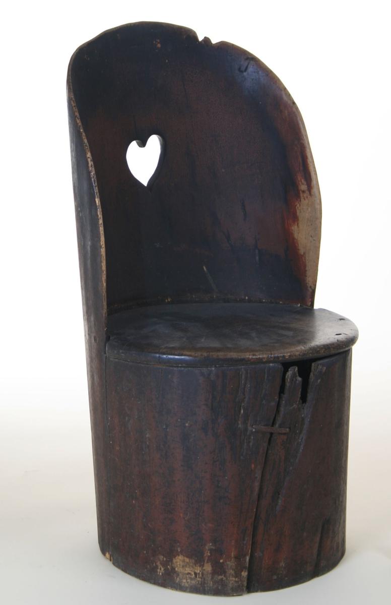 Kubbestol av forholdsvis spinkle materialer, hjerteformet utskjæring i ryggen, tilnærmet ovalt sete.