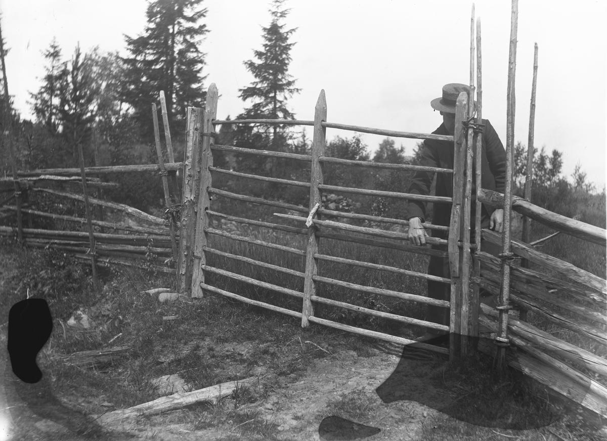 """""""Värmland. Jösse hd. Mangskog sn. Grind, stänges genom att den rörliga käppen i midten skjutes in mellan störarna i gärdesgården."""""""