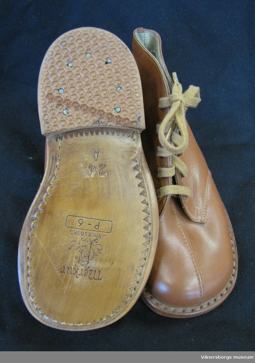 """Bruna barnskor i läder. Snörning med bruna skosnören. Storleken är 24 A. Märket """"Merkur"""" är tryckt under skosulan, samt initialerna """"A F C"""" som monogram och """"Vänersborg"""". Även """"P - 6"""". Skorna ligger i sin originalkartong."""