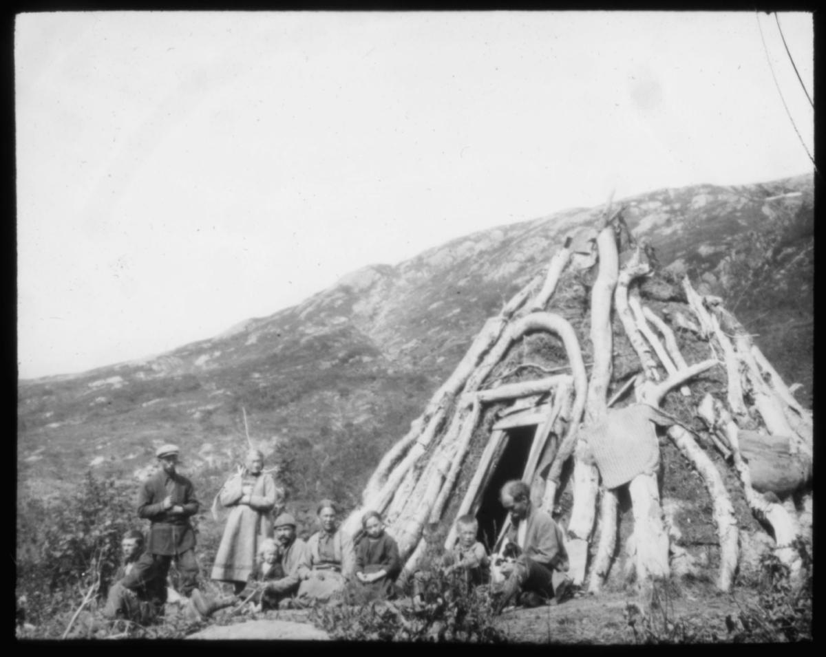 """""""No.596.a) Fra Holmvannet. Dg. 2/8."""" Portrett ved gamme. Utenfor gammen står og sitter det en gruppe samer. De fleste har på seg samiske klær. Gammen er bygget av torv og stammer fra bjørketrær. I bakgrunnen ligger det et fjell. Det er sol og sommer."""