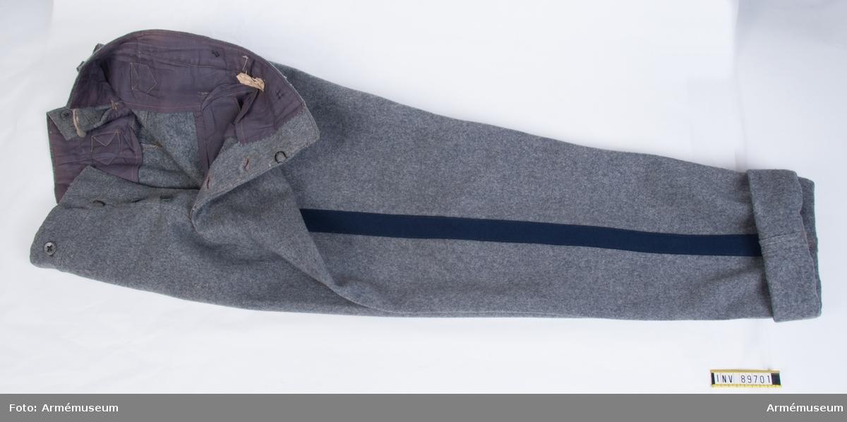 Långbyxor av grått kläde med blå revärer på utsidan av benen.