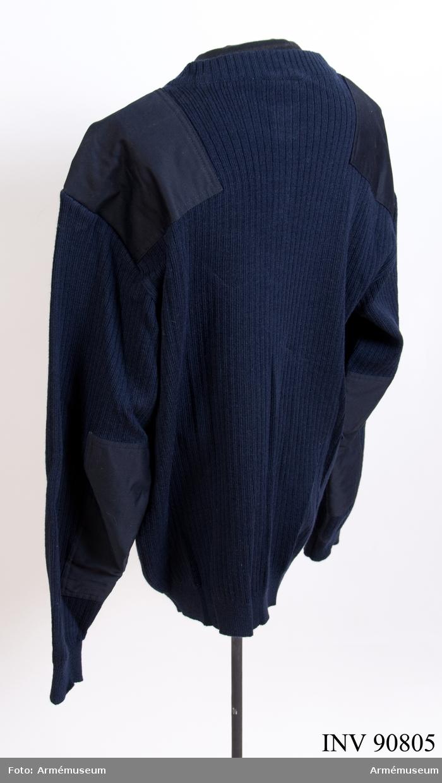"""Stickad tröja av ull med vävförstärkningar på axlarna. Vidhängande etikett: """"Försvarets materielverk, fastställs, M 7321-205000-2, Ylletröja vävförstärkt olivgrön. M 7321-224000-9, Ylletröja vävförstärkt blå, 1991-12-20, H. (oläsligt), cmfT, FMV 267.3. (FMV:Bekläd) 85-09. 1000 Ex"""". Etikett på insidan: """"M 7321-224000-9, 1989, 6, Remploy, tillverkad i Storbritannien, 80 % ull 20 % polyamid, skötselanvisning""""."""