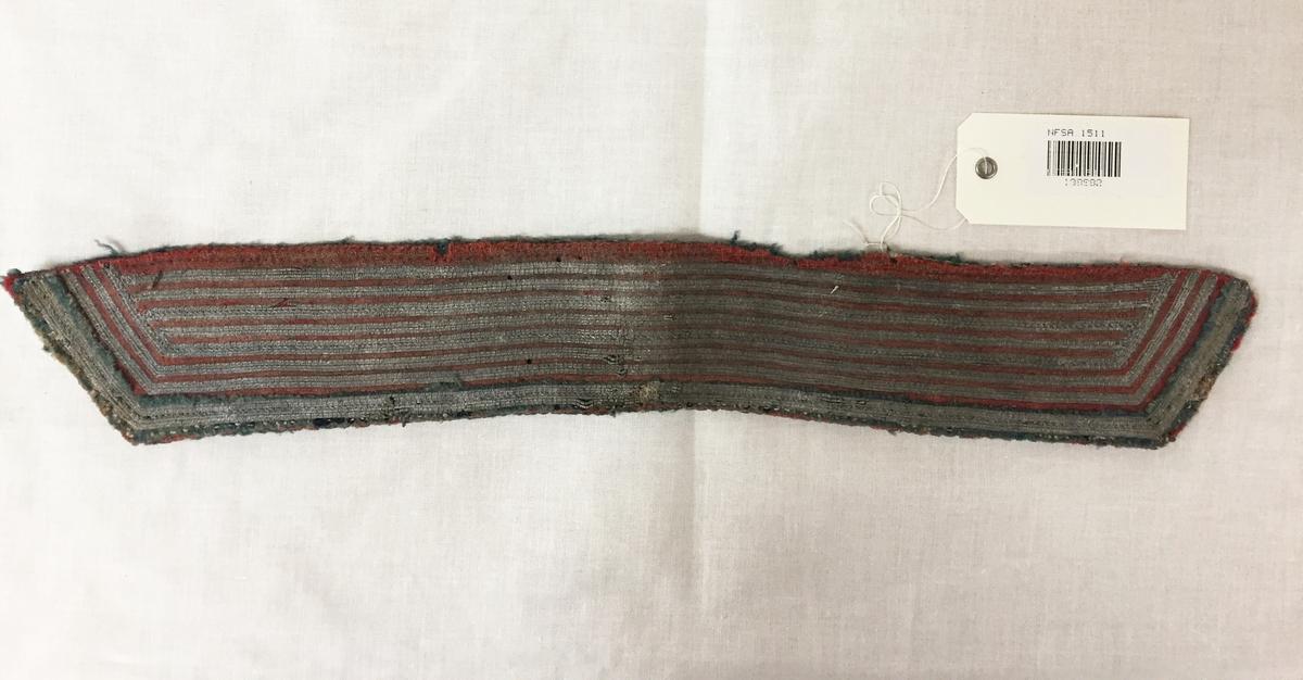 Kragestykke med blå og røde tekstilapplikasjoner, fremsiden er dekket med rader av tinntrådarbeid.
