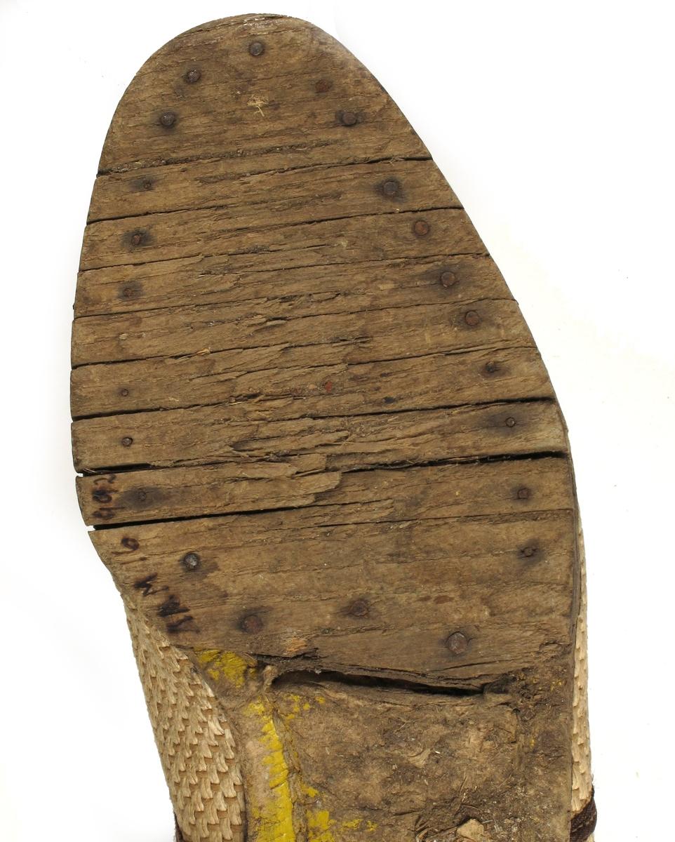 Damesko, krisevare fra tiden 1943 - 45.   Såle tre, leddet. Hælen har gummi ytterst. Mellom sålen og overdelen er der pressa  papp, gulmalt. Overdelen beige,  vevd stoff der renning og innslag  et tvinna papirprodukt. Tå og hælkappe  samt åpninga foran av fiskeskinn.  mellombrunt. Brune bånd. tekstil, sydd rundt åpninga og dessuten som buet pynt  tversover. Snøring og 5 maljer