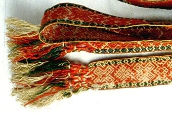 Bälte vävt i upphämta med gråvit botten och mönstertrådar i rött och grönt.Fransar i båda ändar. Okänd härkomst