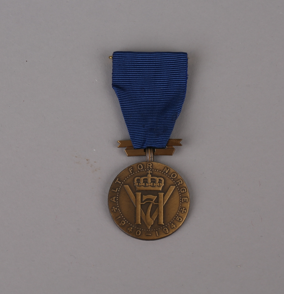 "Bronsemedalje ""Alt for Norge 1940-1945"" med Haakon 7. monogram med tekst på forsiden samt kransdekor på baksiden."