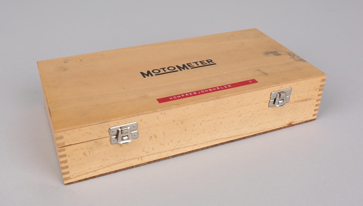 Kompresjonsmåleinstrument i treskrin med diverse deler og bruksanvisning.