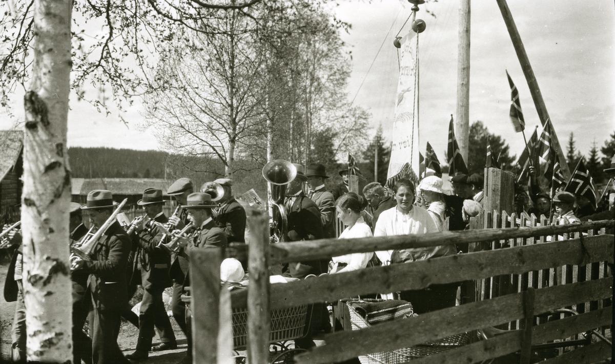 17. mai-tog med hornmusikken på Østby i spissen. Fra venstre: 1) Arve Johansen Haugen (18/11 1891 - 1961) 2) Otto Johansen Haugen (21/8 1897 - 1952) 3) Ole Johansen Haugen (11/11 1878 - 1959) 4) Reidar Østmoe (1903 - 1968) 5) Magnus Johansen Haugen (12/8 1889 - 1961) 6) Helmer J. Bæk (26/1 1870 - 1947) 7) (han med tubaen) Gunnar Bjørseth (17/10 1904 - 1982). Kvinnen under fanen som ser hit: Paula Hemstad g. Ås (1905)