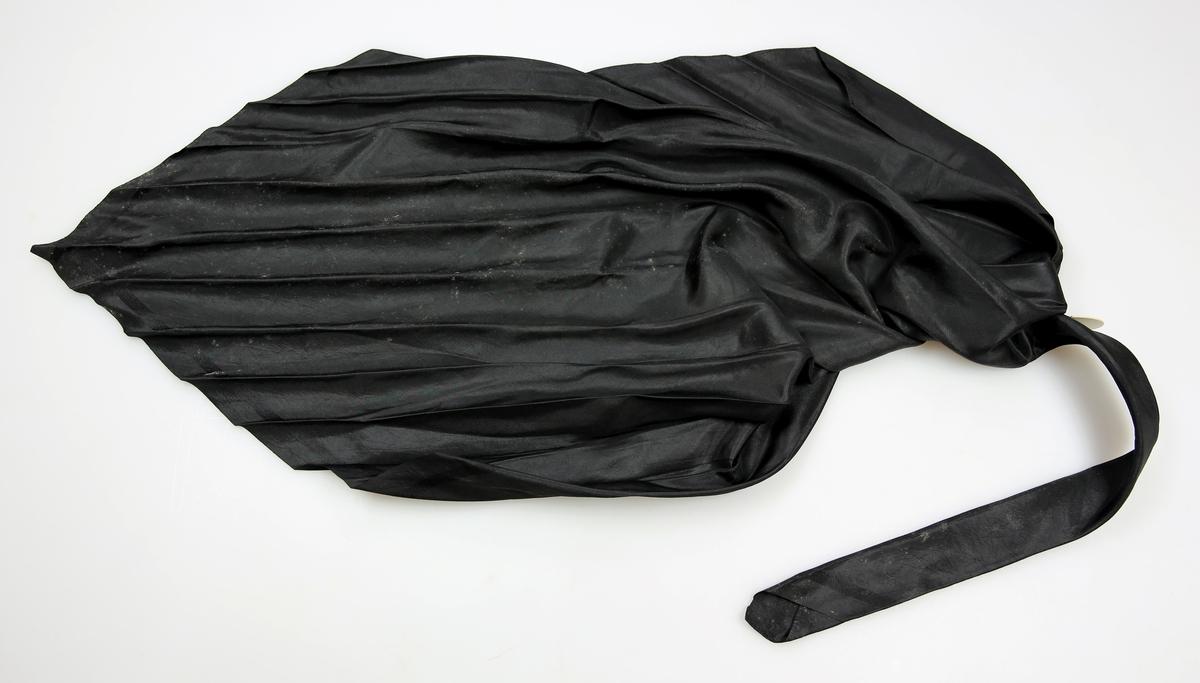 Svart, litt stivt silketørkle brettet som halstørkle. Full vevbredde. Faldet inn for hånd på to kanter.