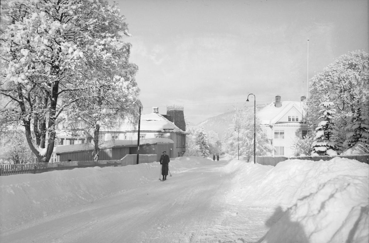 Gatebilde fra Kirkegata med mann på ski. Horsters Minde til venstre.
