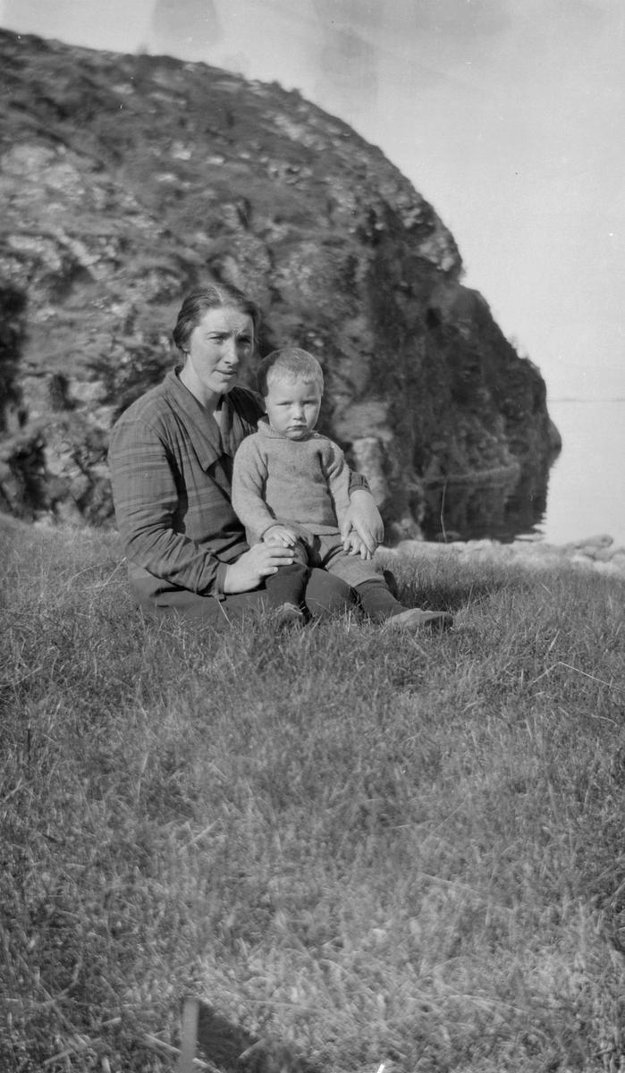Kvinne og en liten gutt sittende i gresset.
