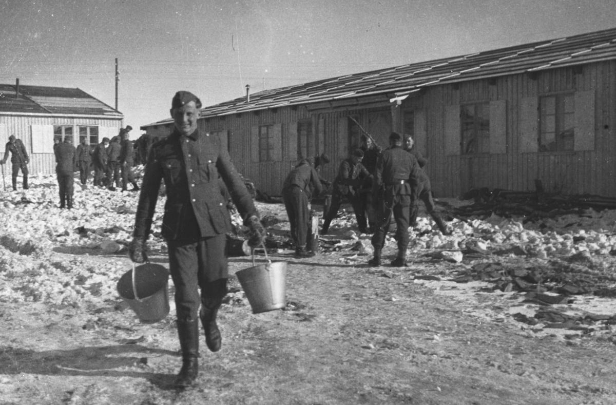 """På vårparten 1941, tyske soldater hakker is ved brakker """"Lager I"""" i Vadsø. Fotografert av en tysk soldat i 1941 Matthias Schlagwein."""