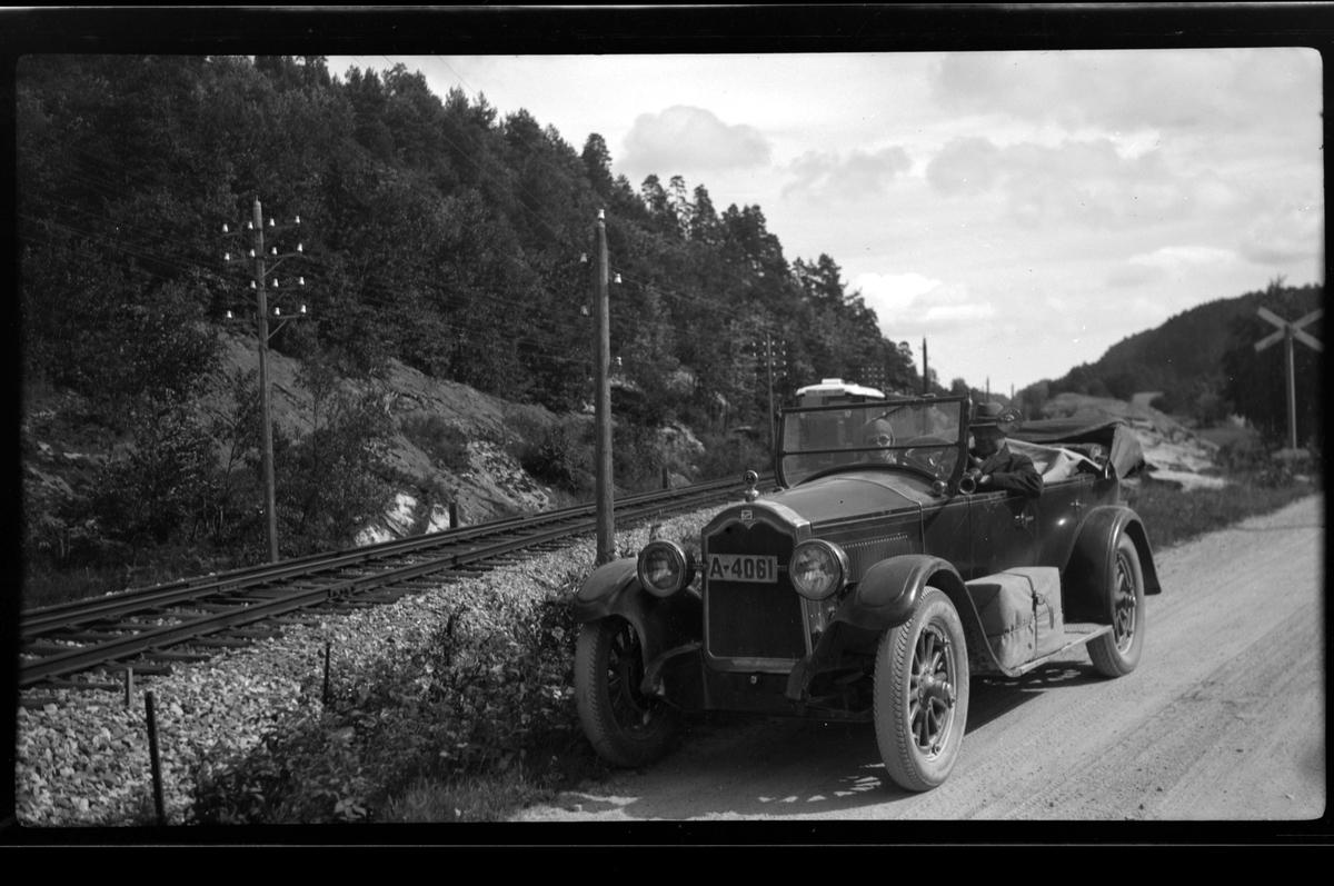 Far og sønn Rolf Sundt sitter i bilen ved Flaksvannbanen i Lillesand, med strømmaster, jernbanespor og skog i bakgrunnen.