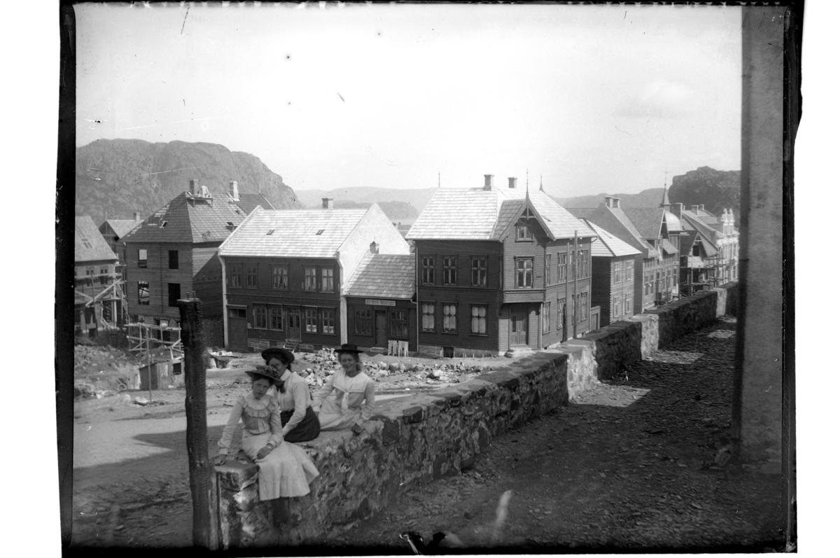 Tre unge jenter foran kirkeruinen, etter bybrannen 1901, mot Nytorvet i Farsund. Fra venstre ukjent, Tiljen Thurmann-Andersen og Plata Atlanta Buch. Fotografert 1903.