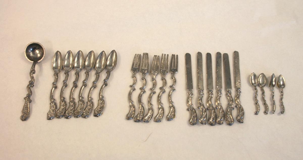Bestikk i 22 deler består av:  A) Suppeøse, med langt dekorert og utformet håndak helt ned til øsen, usymmetrisk skaft med S-former.   B-G) 6 kviner, langt knivblad, med dekorert og utformet håndtak, usymmetrisk skaft med C- former.  K-L) 5 gafler, med tre tinder/pigger og dekorert håndtak, usymmetrisk med C-former.  Q-R) 6 Skjeer, med spiss form, usymmetrisk skaft med C-former.  S-V) 4 Teskjeer, tynt usymmetrisk C-formet skaft.