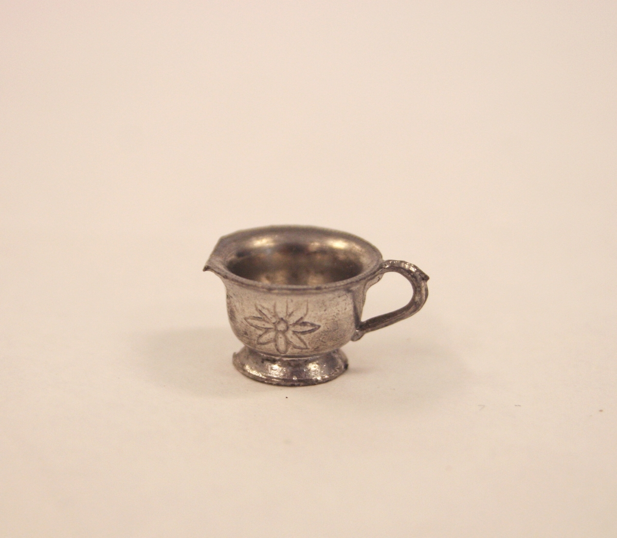 A) Eske:  Perlestav rundt kanten av lokket i gull.  B) Serveringsfat: Riflet kant med dekor under kanten og på fatet. I midten er et blomsterdekor.  C) Tekanne: Mønstret dekor på lokket, blomsterdekor på hver side av kanne.  D) Fløtemugge: Riflet kant på toppen med blomster på hver side av muggen.  E) Tekopper: Riflet kant øverst på koppen rundt, blomsterdekor på hver side av koppen.  F) Teskål: Riflet langs kanten hele veien rundt.  G) Serveringsbolle: Møstret og riflet kant med prikker rundt hele.  H) Duk: Heklet broderi, blomsterlikning.