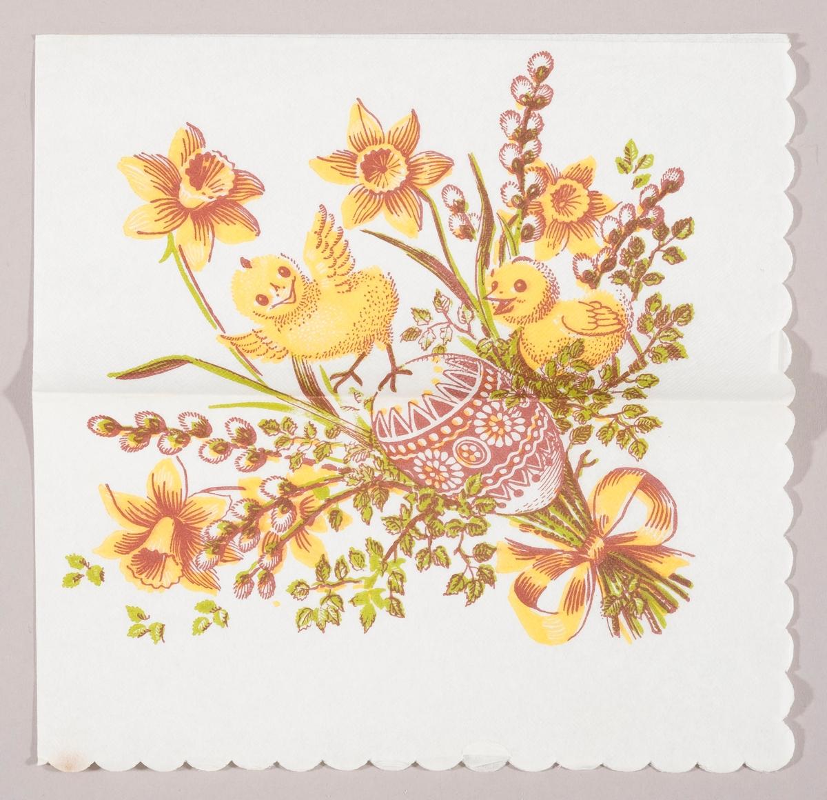 """En bukett med påskeliljer og grener med """"gåsunger"""". Et dekorert påskeegg og to kyllinger er er plassert i buketten. En sløyfe holder sammen på buketten."""