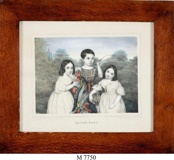 """Litografi (delvis färglagd).  En pojke på en gunghäst och två flickor. Under bilden tysk text: """"Spielende Kinder"""".  1840-tal."""