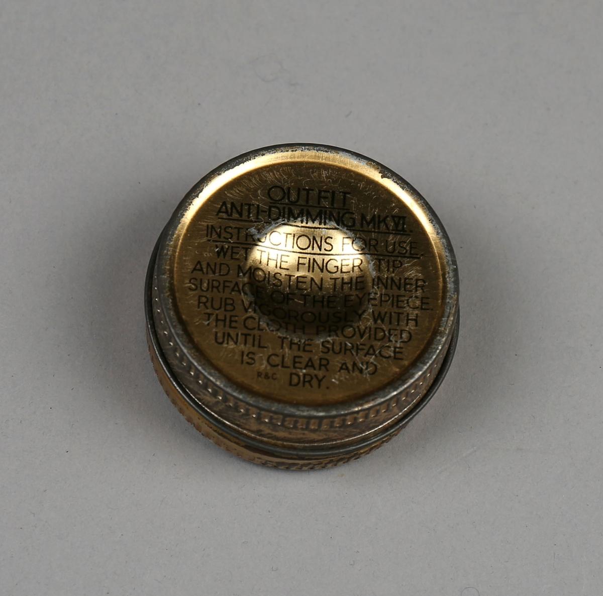 Liten rund beholder i metall med lokk. Inneholder en liten pusseklut. Oppbevares i lomme i tøyveske til gassmaske.