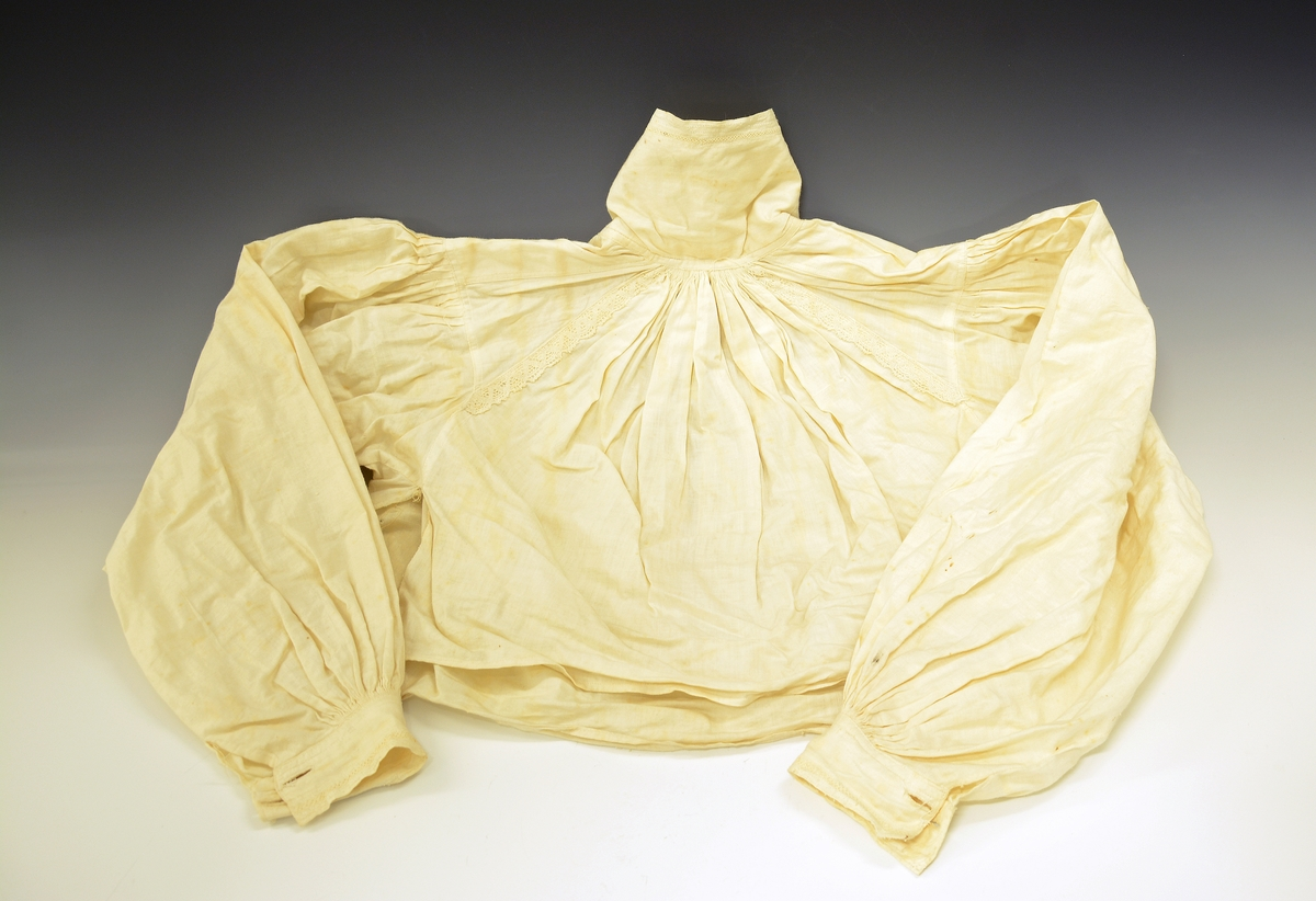 Kvinneskjorte. Kvindedragt fra Sætesdalen. k) Kvindeskjorte med kjøpekniplinger paa ermer, halsline og bak paa skulderstykket. Rundrynket; halslinen høi. Protokoll: Skjorten tilhører drakt: TGM-SM.1192.A-O
