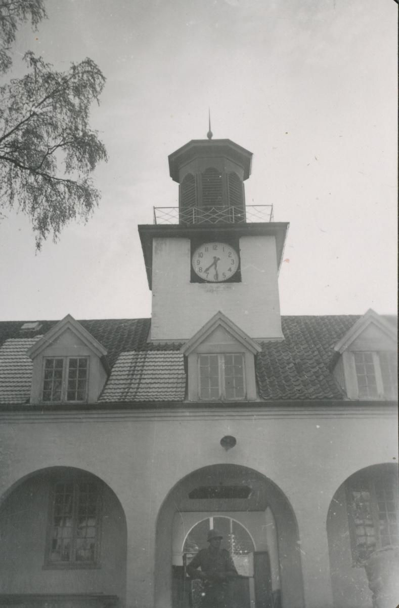 En vakt står under klokketårnet på Falstad fangeleir 12. mai 1945.