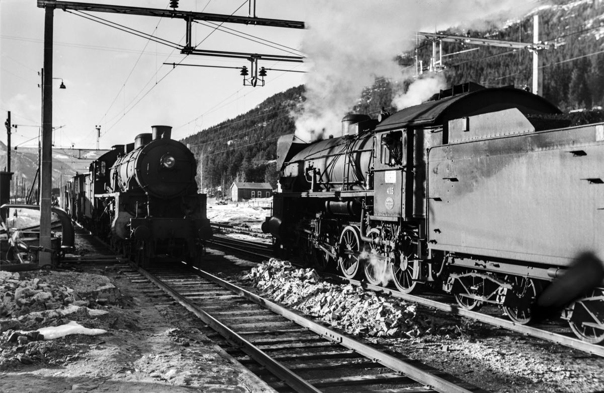 Kryssing mellom godstog til Bergen og godstog 5532 til Hønefoss på Nesbyen stasjon. Toget til Bergen trekkes av damplokomotiv type 31b nr. 418, tog 5532 trekkes av damplokomotiv type 31b nr. 449.