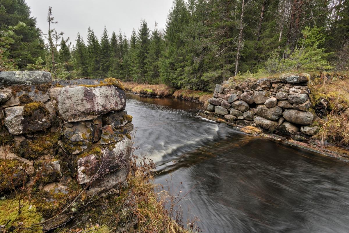 Nysæterdammen eller Tverrendammen i elva Tverrena, som renner fra Trysil mot Åmot kommune, der den renner ut i den nordøstre enden av Osensjøen.  Dette fotografiet er tatt på tvers av vassdraget der hvor elva renner inn i damløpet, fra øst mot vest, på motstrøms side.  Nysæterdammen er bygd på et sted der Tverrena renner langs en morenerygg på vestsida av elva, mens terrenget på østsida er noe slakere, men med en tydelig elvebakke.  Da dette fotografiet ble tatt, høsten 2018, bortimot 50 etter at fløtinga i dette vassdraget opphørte, var dambrua borte, og det var såpass mye vann i elva at det bare var den østre delen av kulturminnet som ble besiktiget på nært hold.  Nysæterdammen er bygd av stedlig stein, som i liten grad er tilhogd.  Den østre damarmen er 26-27 meter lang og tiltar i høyde mot elveløpet, der bredden på damkrona var om lag 4 meter mens høydeforskjellen ned mot damgolvet ble målt til cirka 2,4 meter.  Her var det visse tendenser til utrasninger.  Dambrua var, som nevnt borte, men dette synes å ha vært en nåledam, jfr. SJF.1989-02797 og SJF.1989-02799.  Et «søkk» i vannspeilet viser tydelig hvor «damstokken», det nedre anleggspunktet for «nålene» (plankene) som ble brukt til å stenge dammen ligger.    Ved enden av den østre damarmen lå det ei koie og en stall, med vegforbindelse til Slettåsvegen (fylkesveg 215).  Det hørte også et redskapshus og en utedo til anlegget.  Mer historisk informasjon om Nysæterdammen finnes under fanen «Opplysninger».