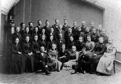 Gruppbild av 37 kvinnor och män, sittande och stående i en h